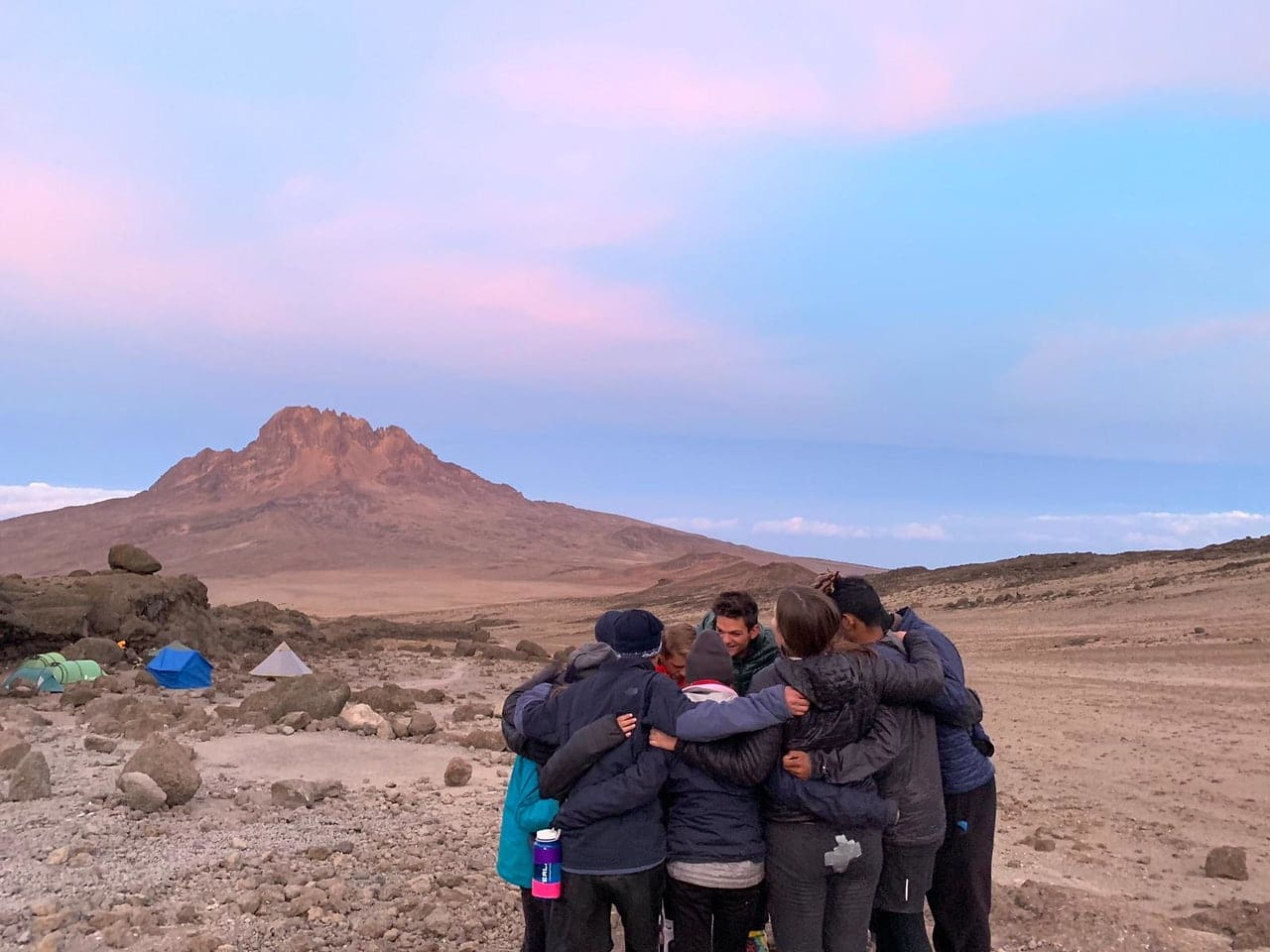 Teens huddle during a summer sunset to reflect on a day well spent hiking in Tanzania