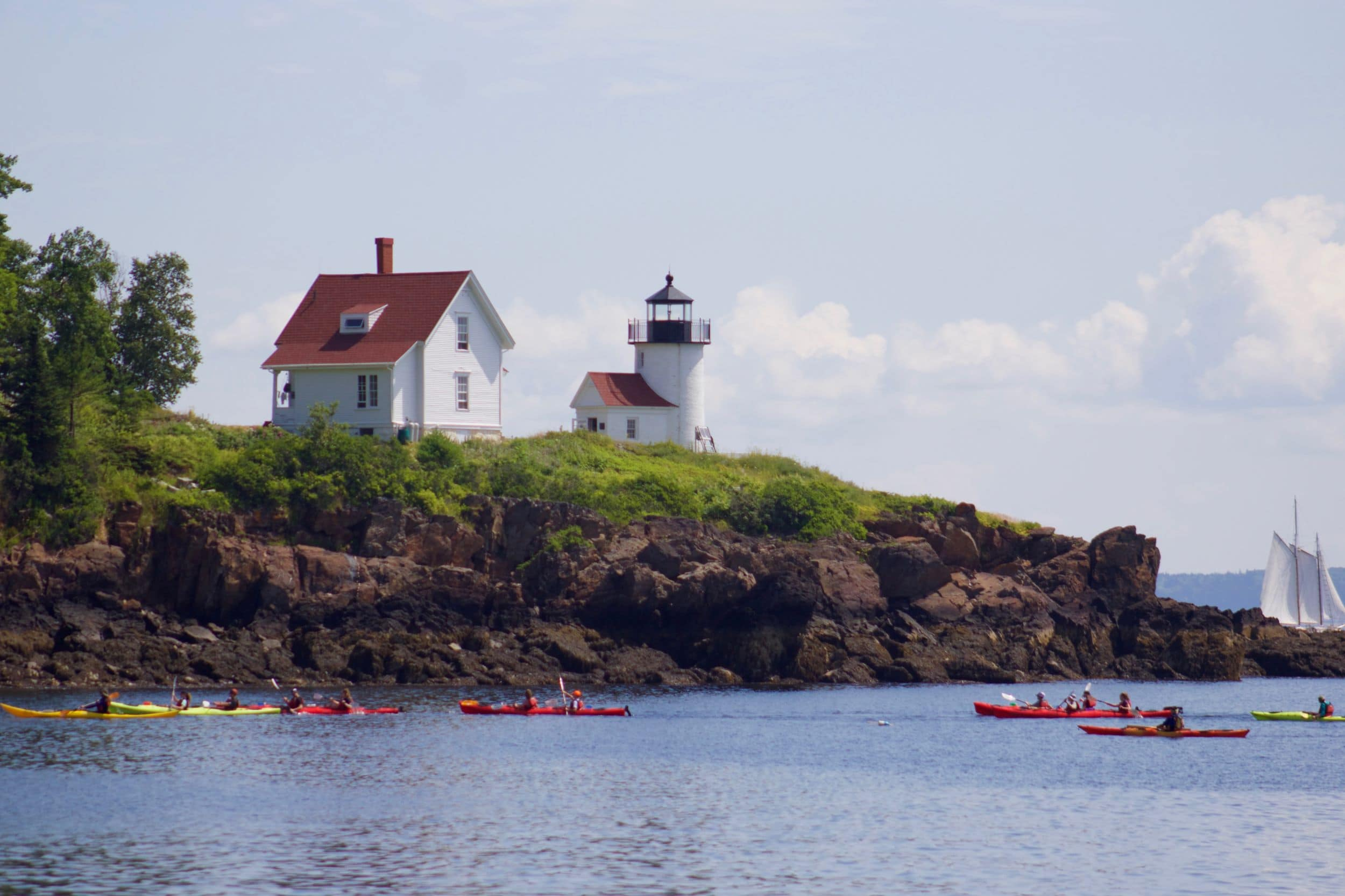 A picturesque day on the Maine Coast with campers kayaking in the ocean during a summer adventure camp