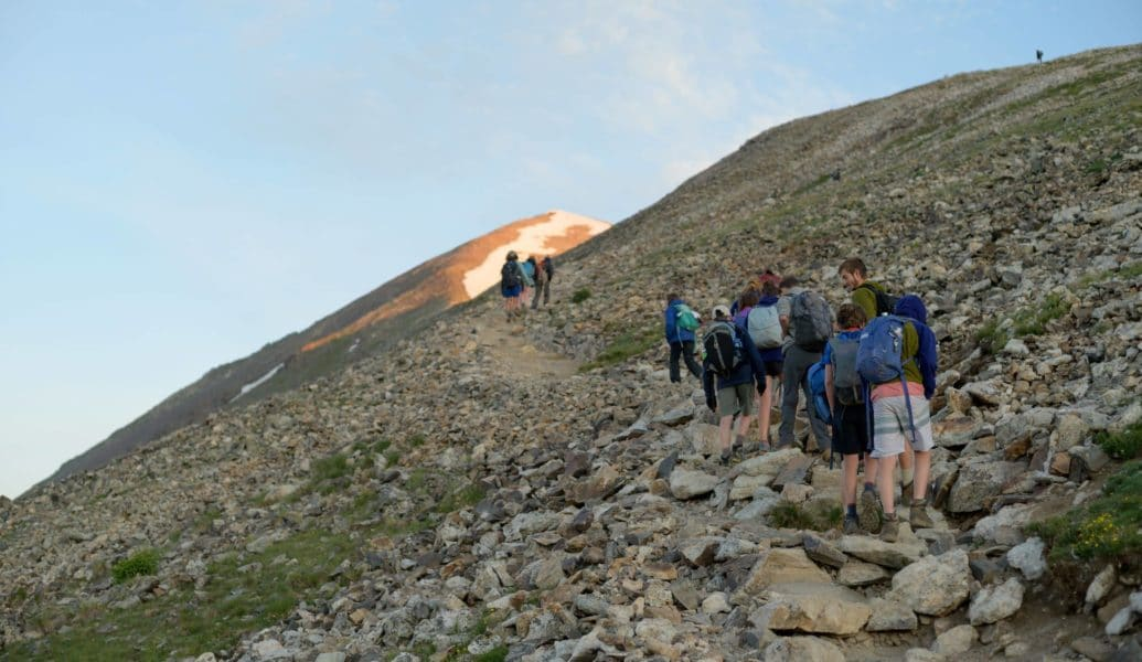 A group hikes up a steep incline this summer on a adventure trip in the Rocky Mountains