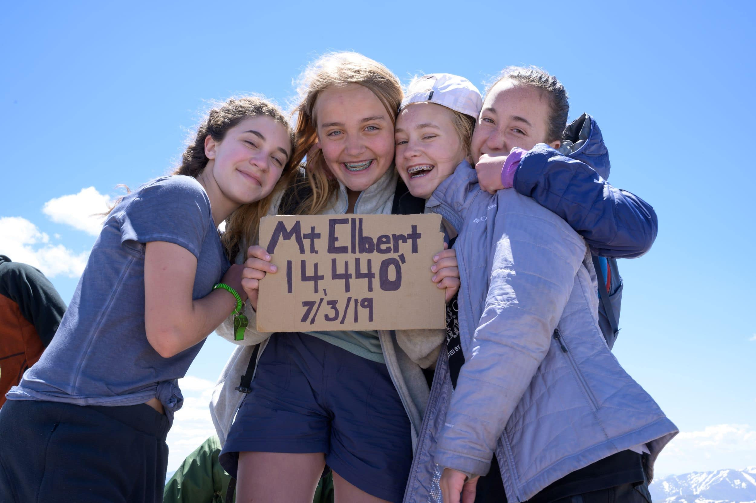 A group of teens celebrating on top of Mt. Elbert this summer on a teen hiking trip