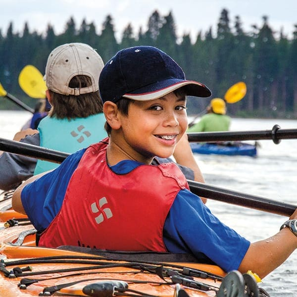 Boy on summer kayaking trip looks back and smiles for the camera
