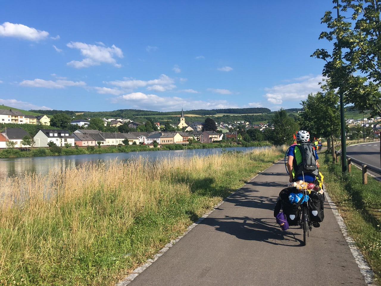 Teens heading into a quaint town on this summer biking trip through Europe