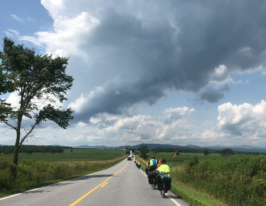 A group rolling down the road on a teen summer biking trip
