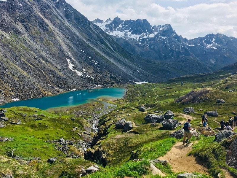 Group of hikers traversing a boulder field during the Alaskan summer