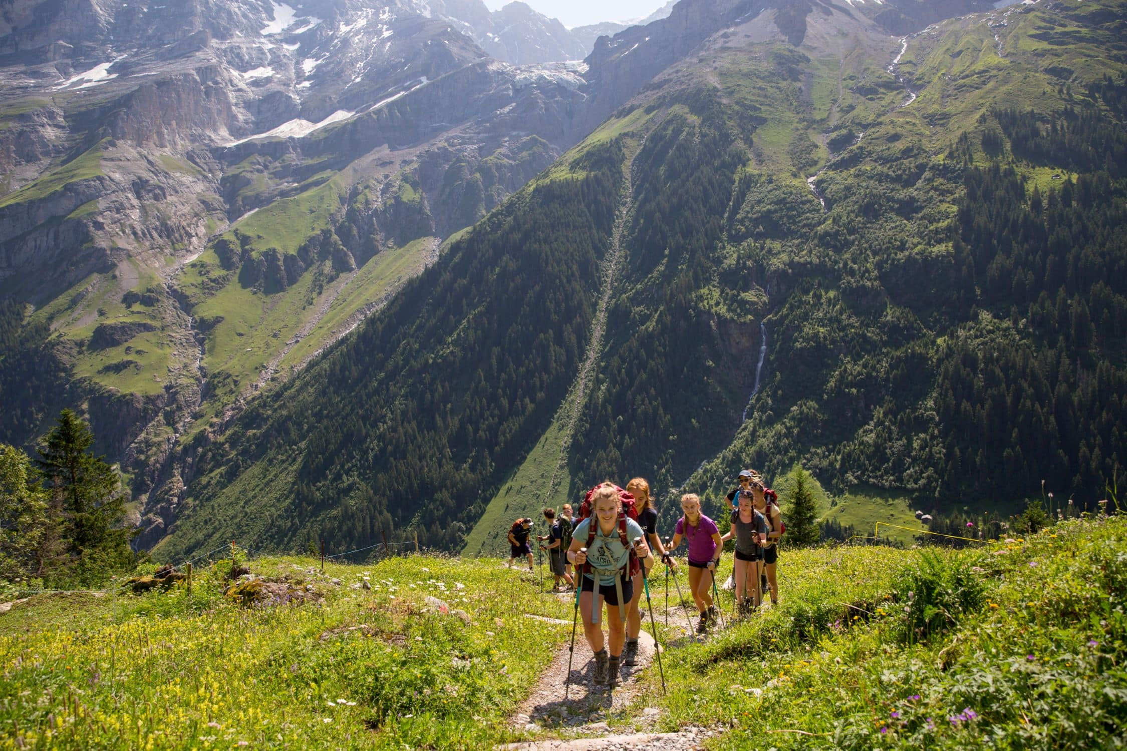 Hikers following a trail into the Swiss Alps on an adventure program this Summer