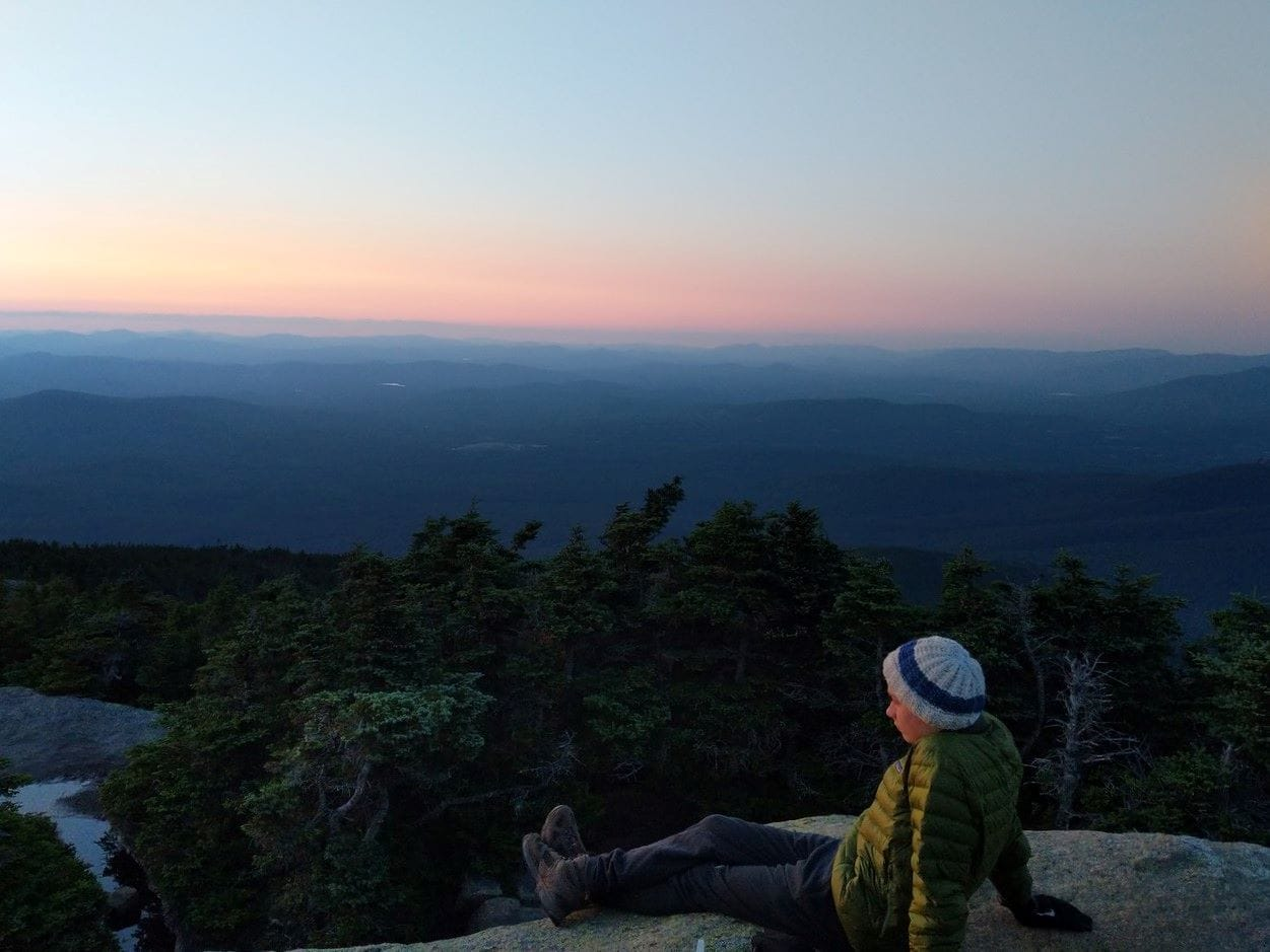 A camper peers out into the distance during a summer sunset while on a hiking trip on the Appalachian Trail