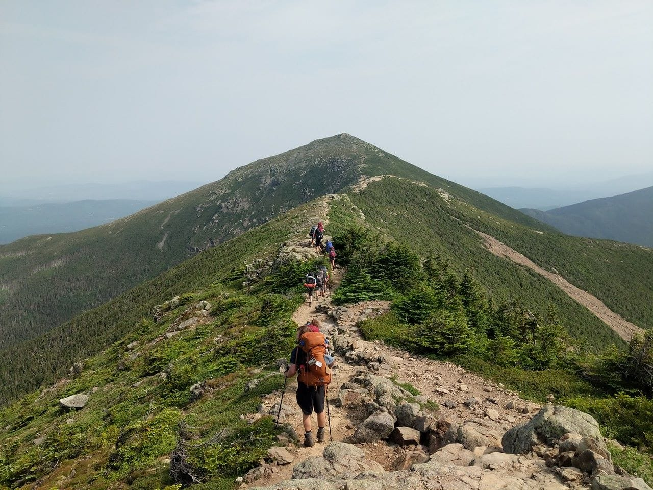 A group of campers ridge running on the appalachian trail while on an overland hiking trip this summer