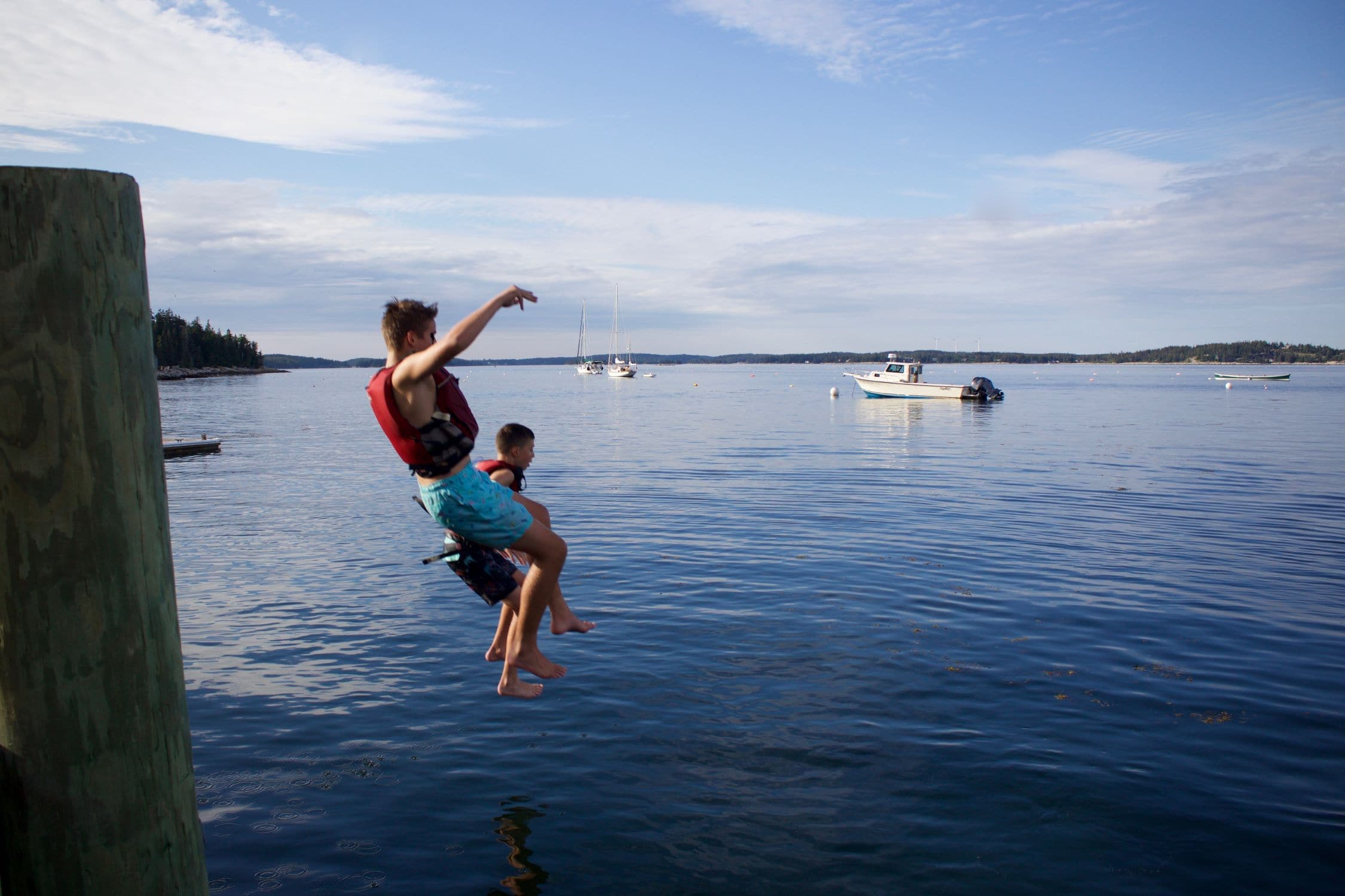 Teens jumping off of the dock on their teen adventure program in Maine this Summer
