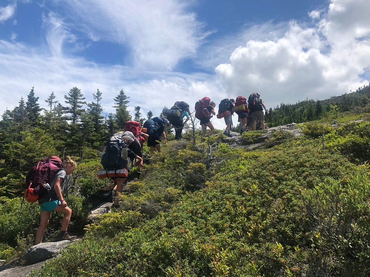 Campers hiking up a steep incline this summer during a teen adventure program
