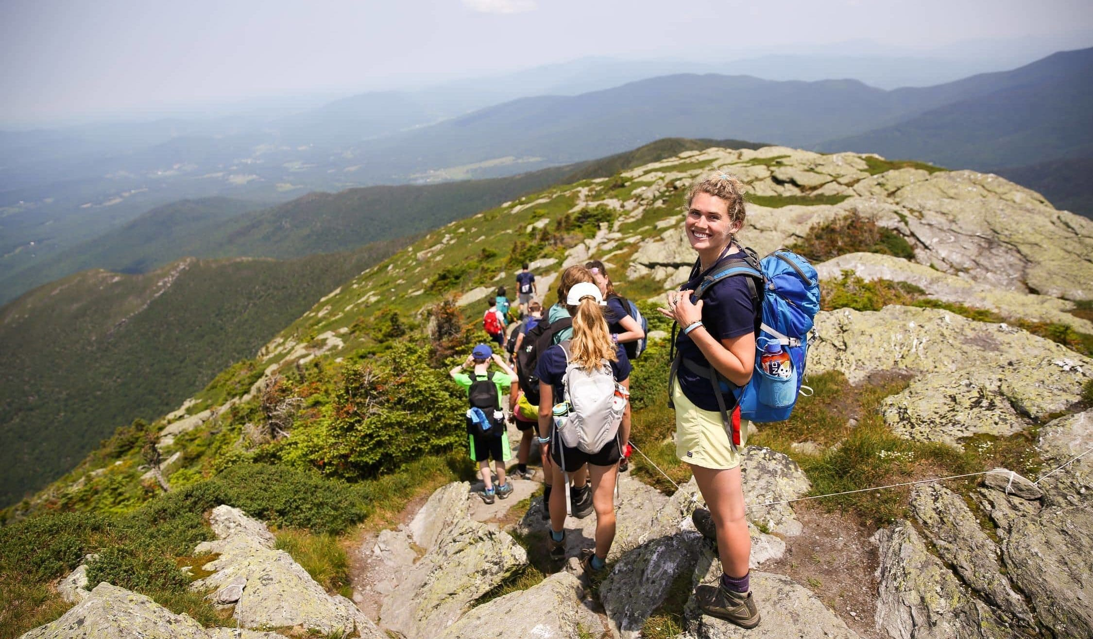 Teens on the summit of a mountain during this summer adventure in New England