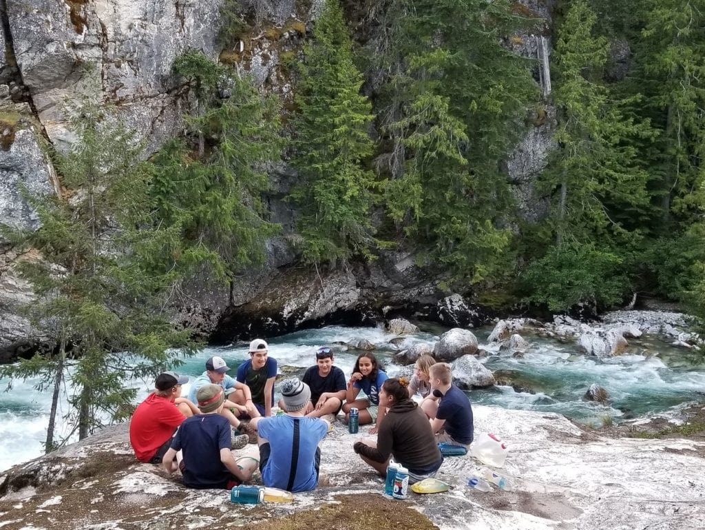 Campers stop for lunch next to a river during a teen adventure program this summer
