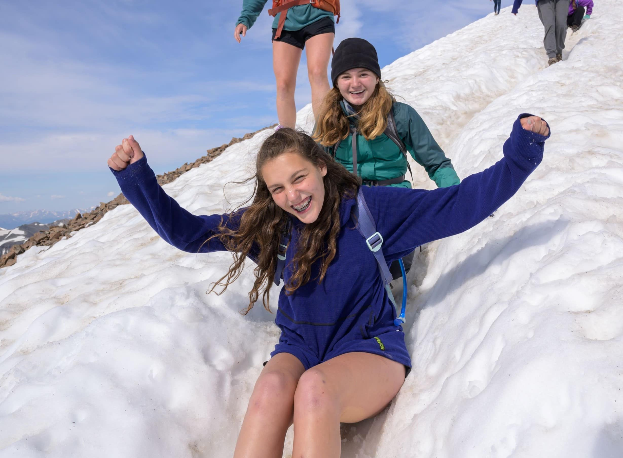 Campers sledding down the mountain on their teen summer adventure program