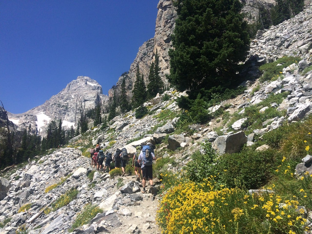 Hikers ascending a mountain on a narrow trail while on a overland adventure program this summer