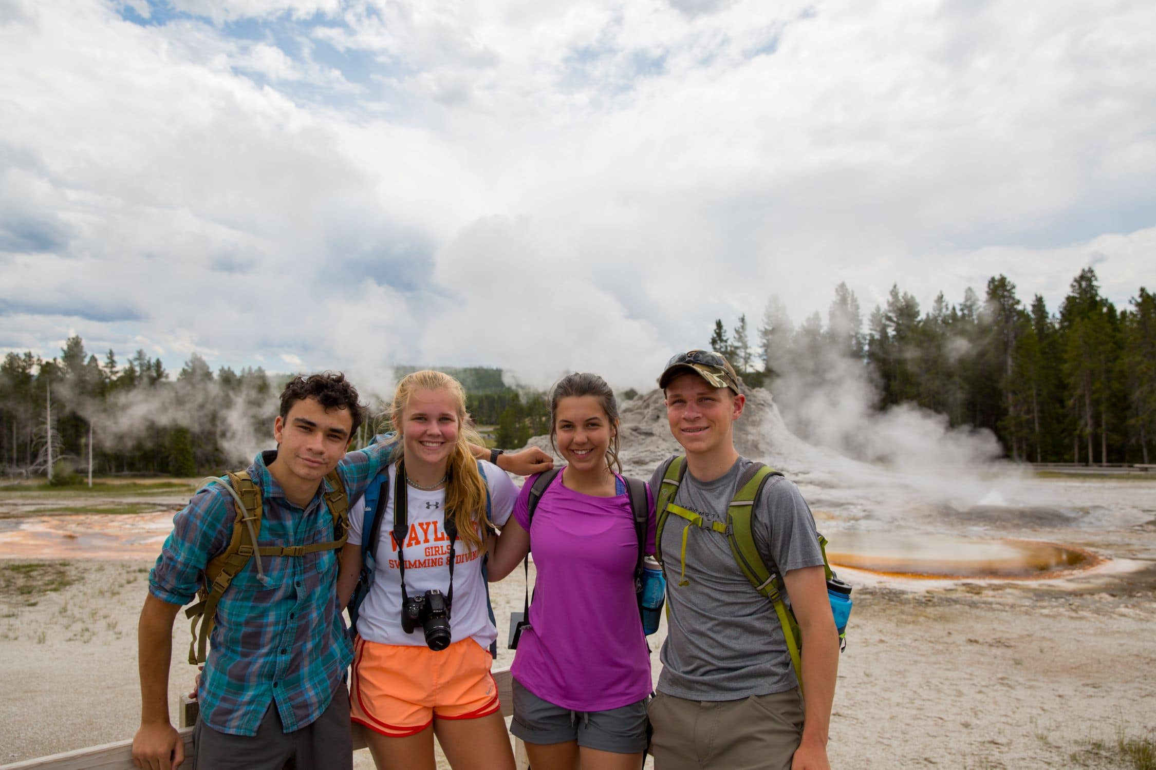 Campers in front of old faithful geyser while exploring yellowstone national park on a teen adventure program