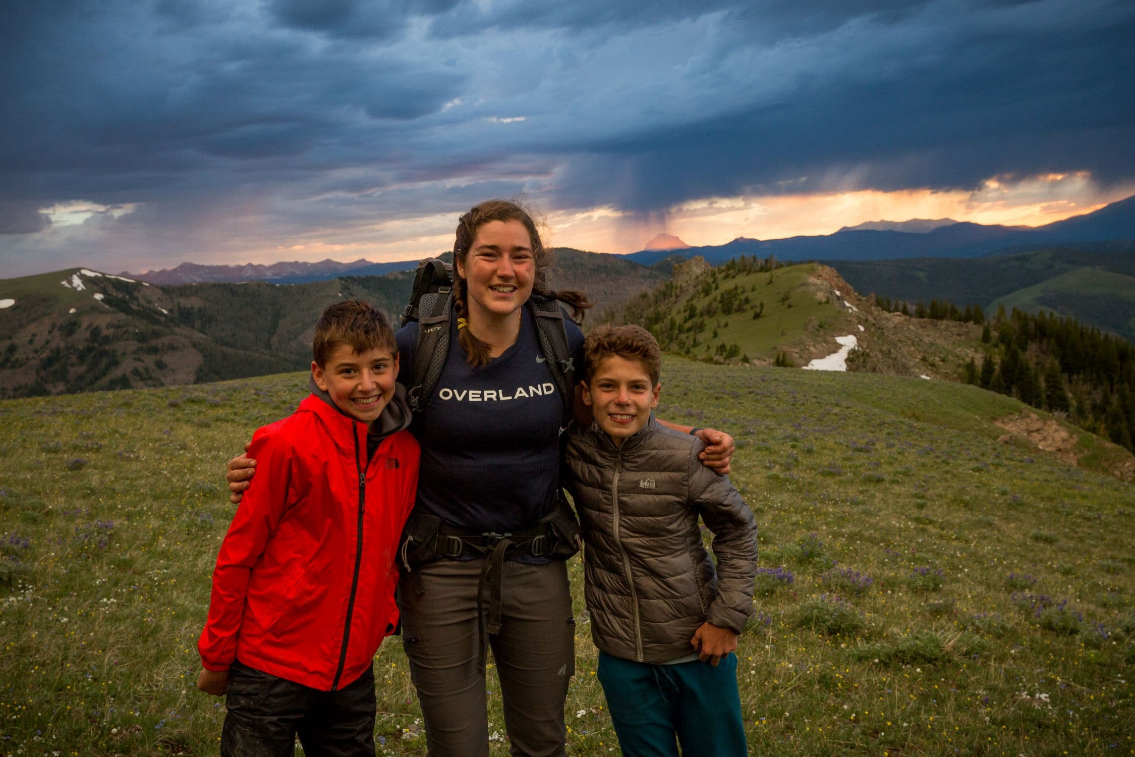 Trip leader posing with two campers on a teen adventure program