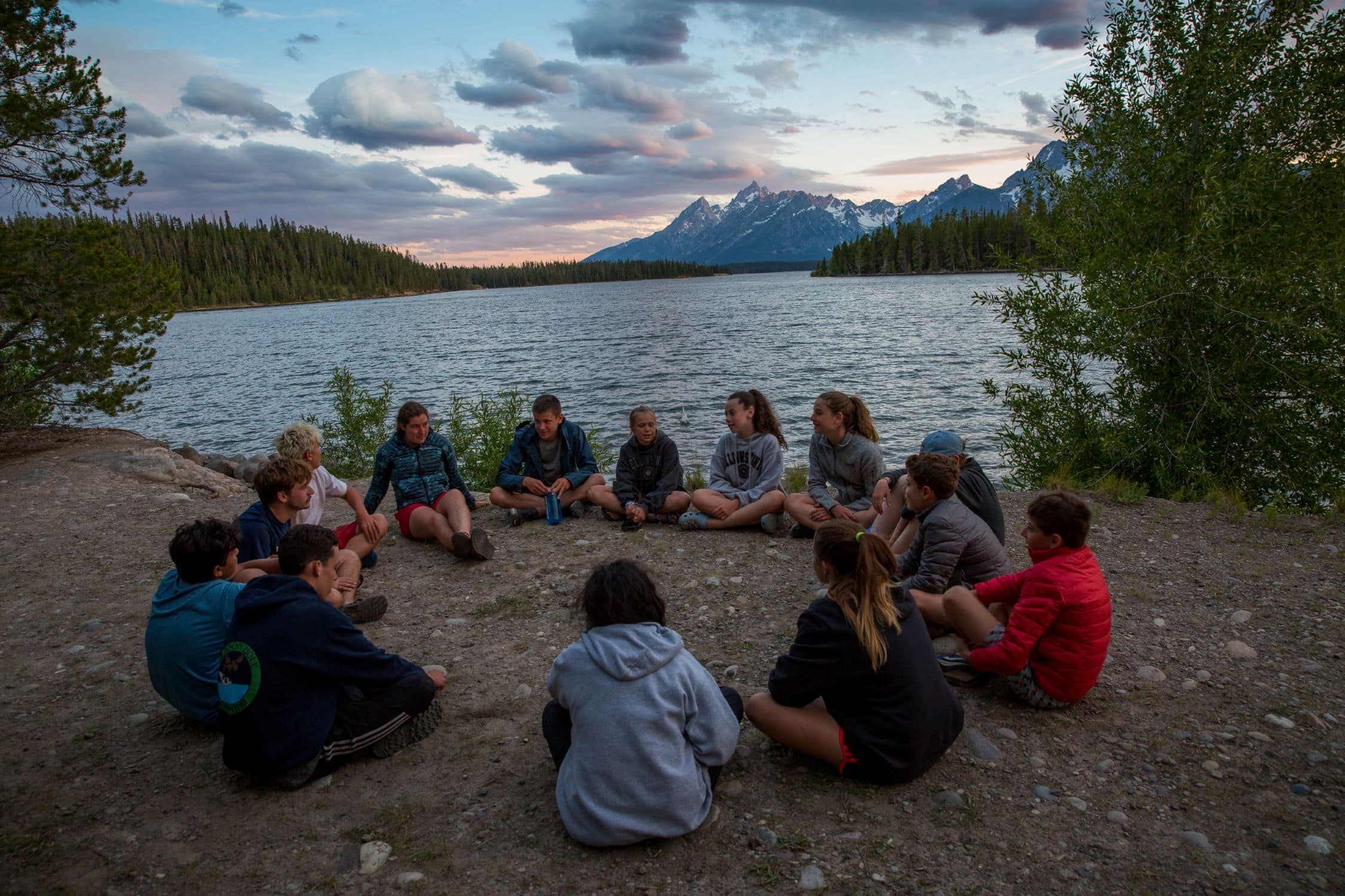 A group of campers reflects upon an amazing day on a teen summer adventure program at sunset