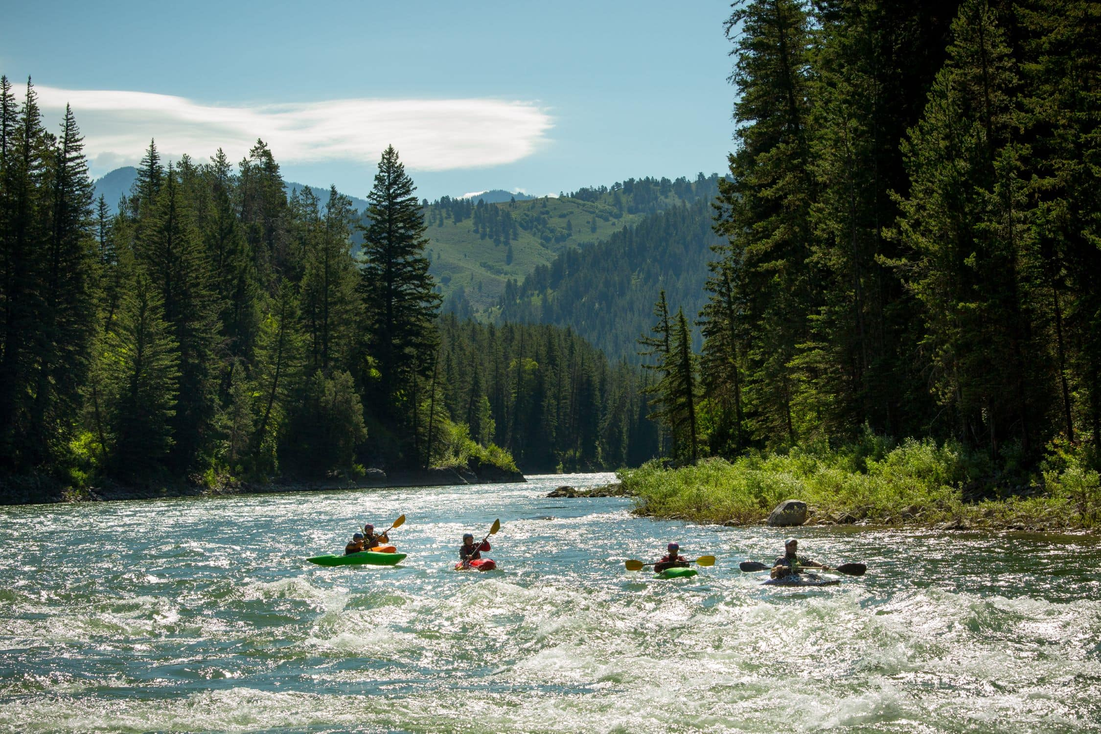 Kayakers float down the river this summer on a teen summer adventure program