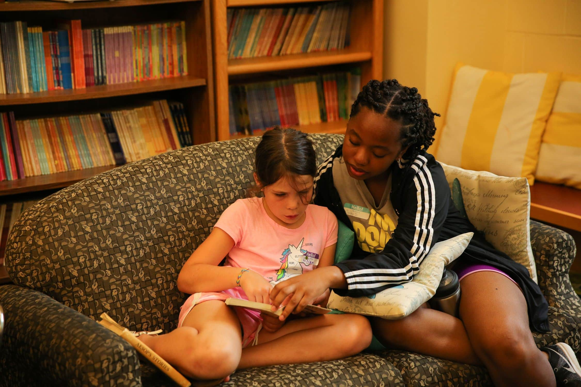 Teen mentoring a child read during a summer service program