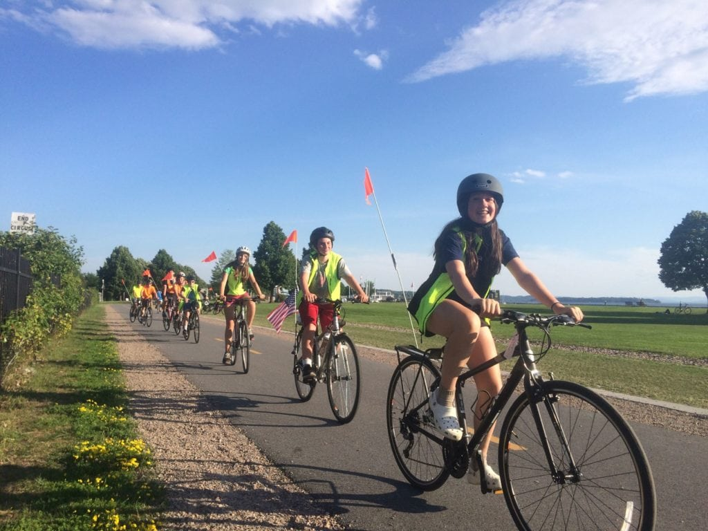 A girl smiling while riding her bike and wearing a helmet in from of the group in Vermont