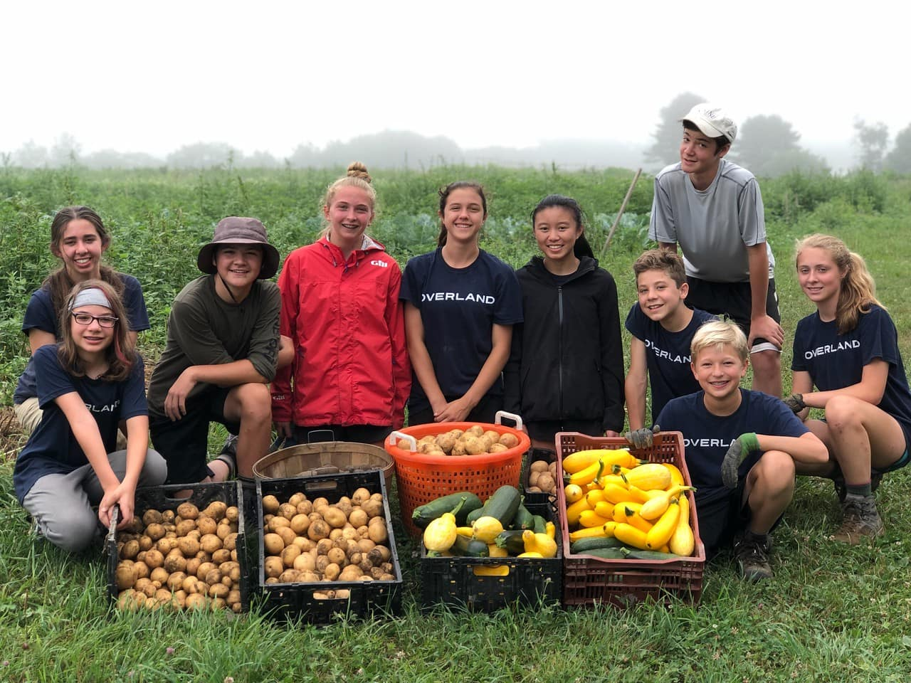 Teens posing with crops picked on their Service and Hiking trip