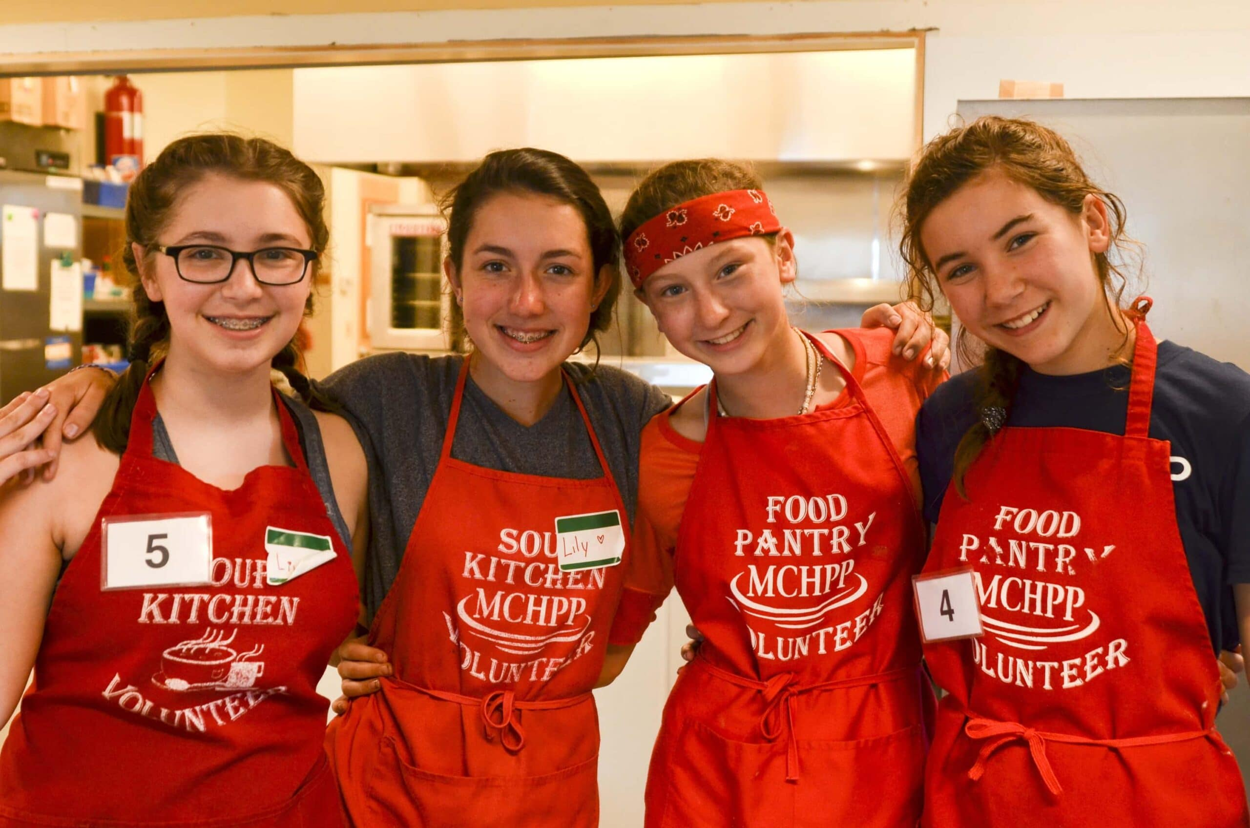 Teens posing and smiling while serving at a food pantry during their service trip to Maine