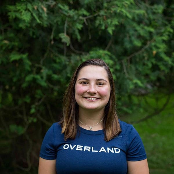 Female team leader standing in front of a tree outdoors while preparing for her teen summer adventure camp