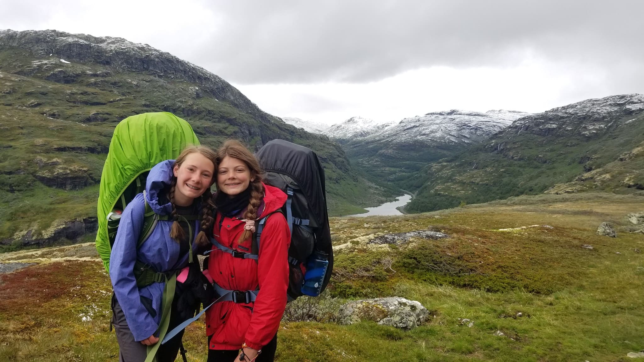 Girls have big backpacks and even bigger smiles when hiking in Norwegian wilderness this summer on an Overland teen summer adventure program
