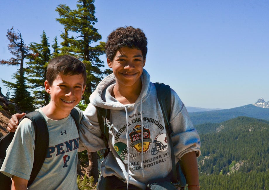 Two hikers rest a moment at the top of a mountain while on their Overland summer adventure program