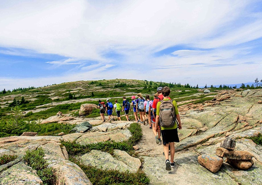 Campers hike single file on a Summer adventure with Overland
