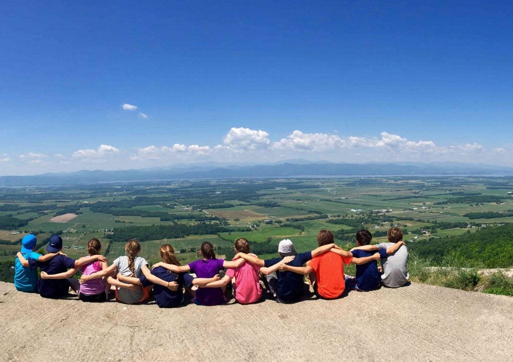 Group of campers taking in a beautiful view while hiking with Overland this summer