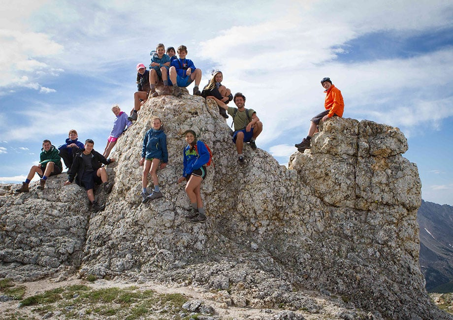 Students on top of a rock face while on a hiking trip with Overland Summers