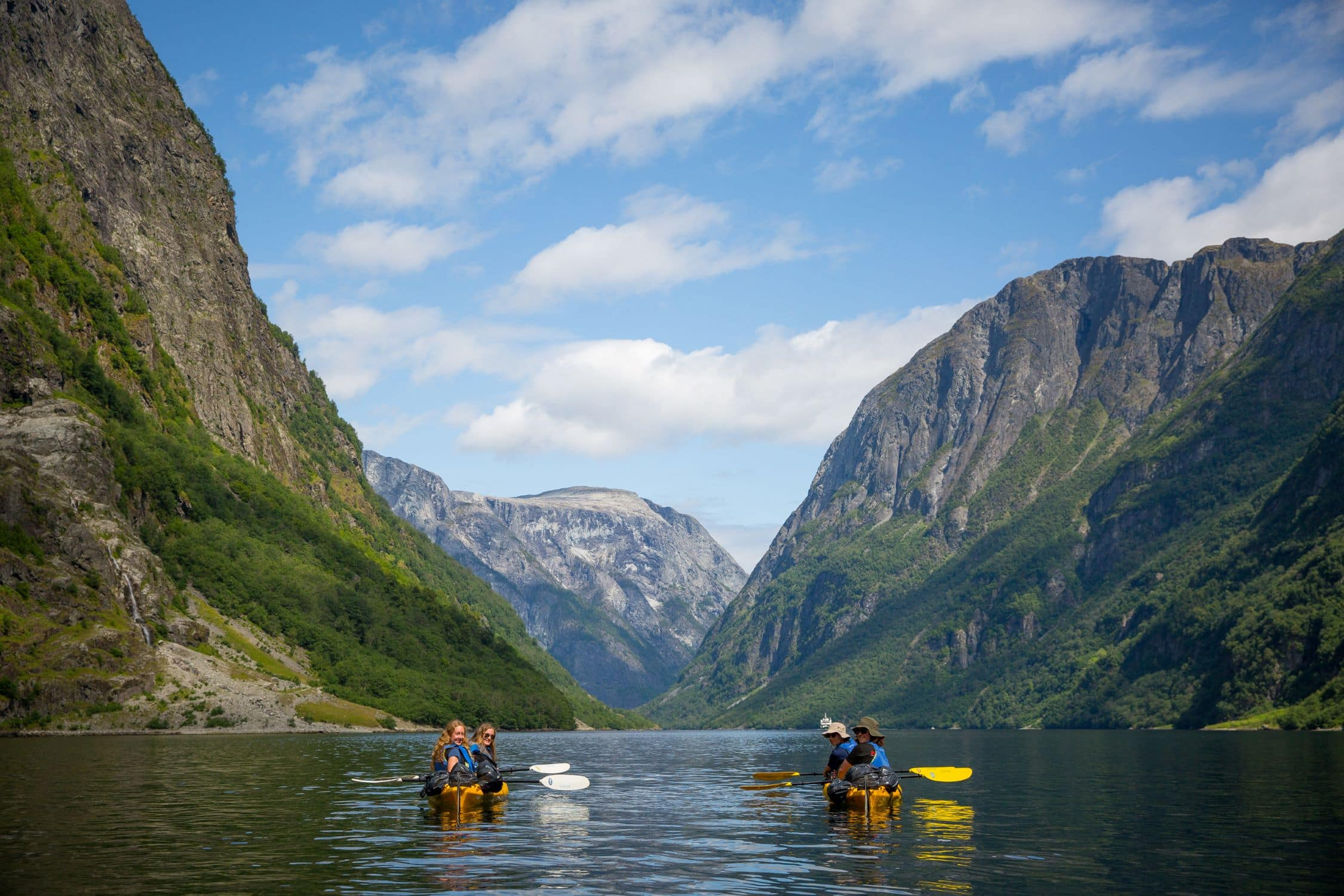 Campers kayaking through a Norwegian fjord this summer on a teen adventure program