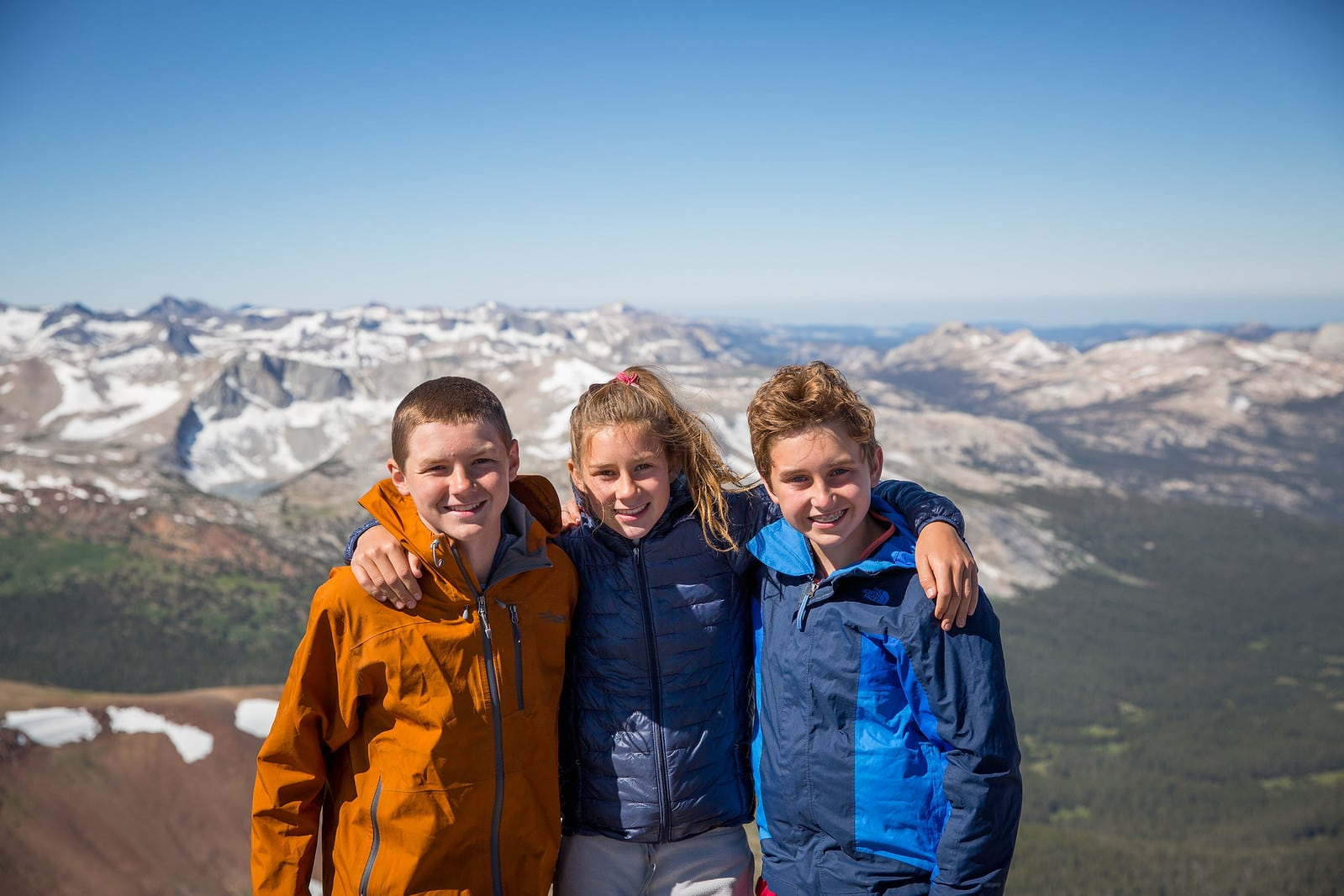 Three friends take a group photo on the summit of a mountain during a teen summer hiking trip