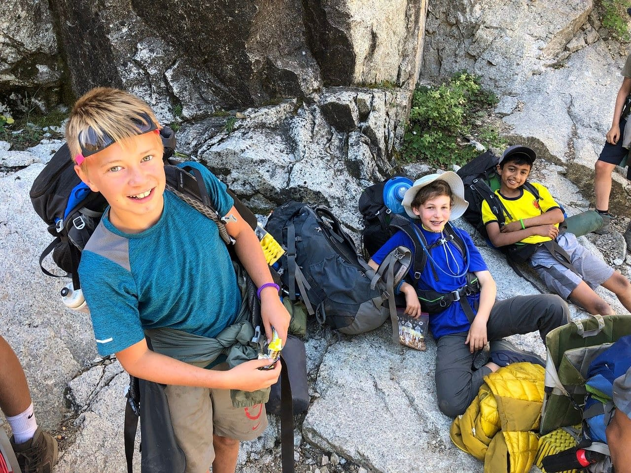 Three friends take a quick break in the shade while hiking in the high sierra this summer on their adventure trip