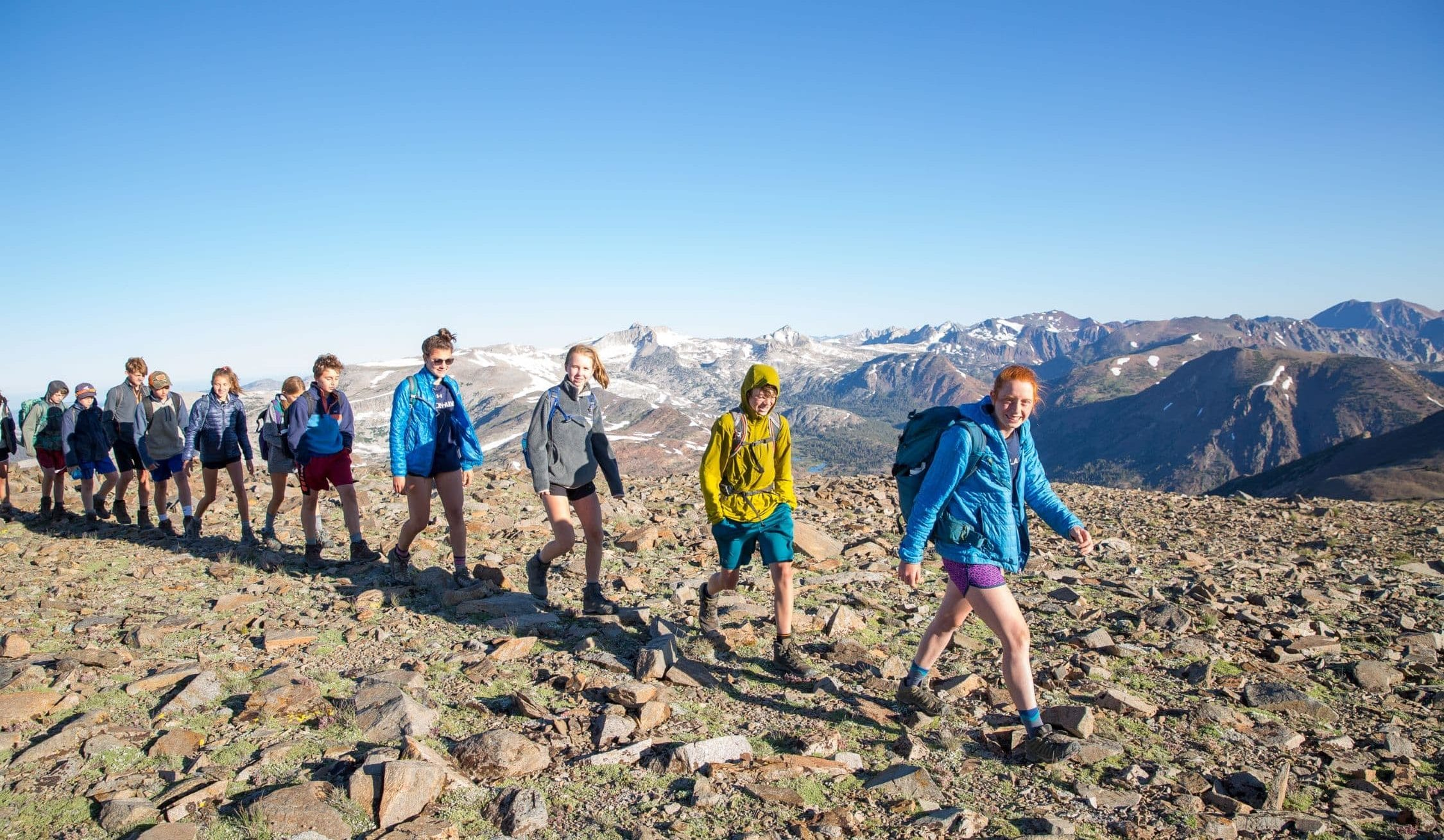 Hiking single file in the High Sierra on a teen summer adventure trip