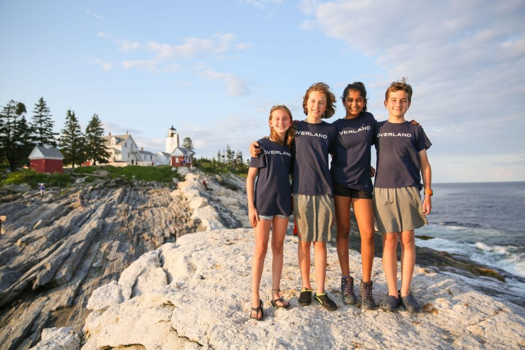 Overland kids pose together in front of a Maine lighthouse during their summer adventure.