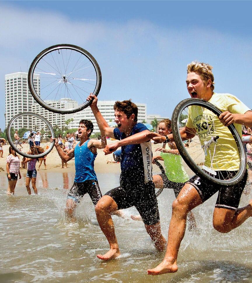Teen run into the ocean after an amazing summer biking coast to coast on an Overland adventure trip