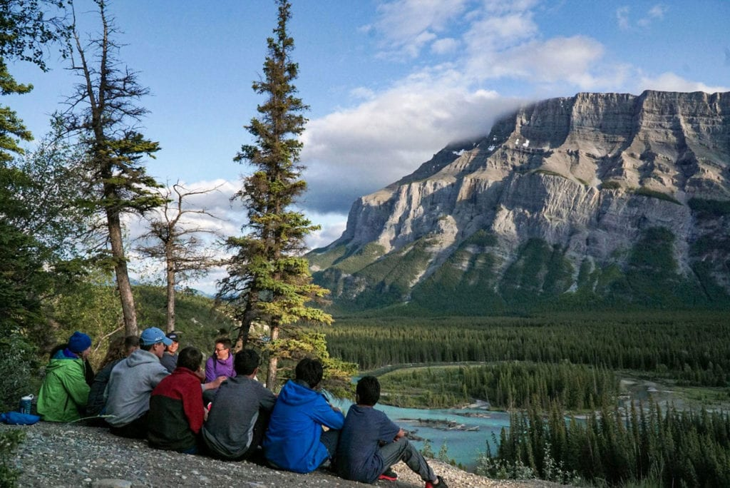 A group pauses to take in the scenery of the Rockies after a long summer day of biking