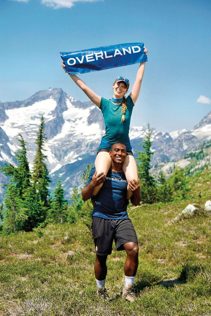 Two leaders pose in front of mountains, with the female lead on her male coleader's shoulders holding a sign reading Overland.