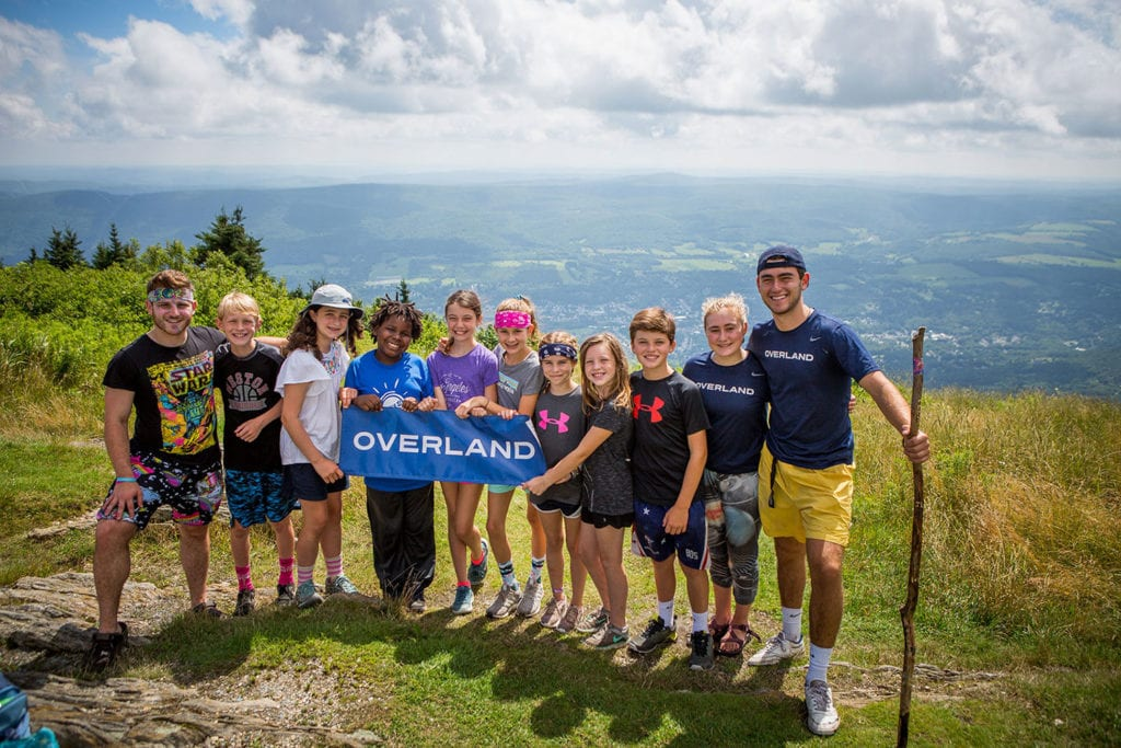 A group and their leaders holding an Overland sign at the summit of Mount Greylock during a summer hiking trip.