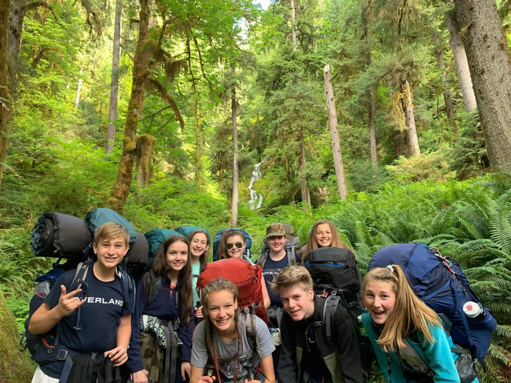 A group smiles together wearing backpacking packs in a forest of the Pacific Northwest.
