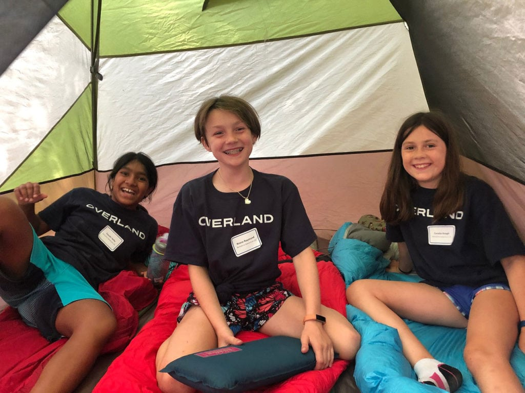 Three girls in a tent smiling on their summer hiking trip in the Berkshire Mountains.
