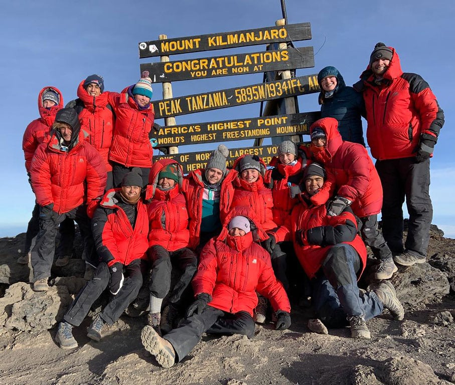 A group at the summit of Kilimanjaro smiling after a challenging hike during their trip to Tanzania.