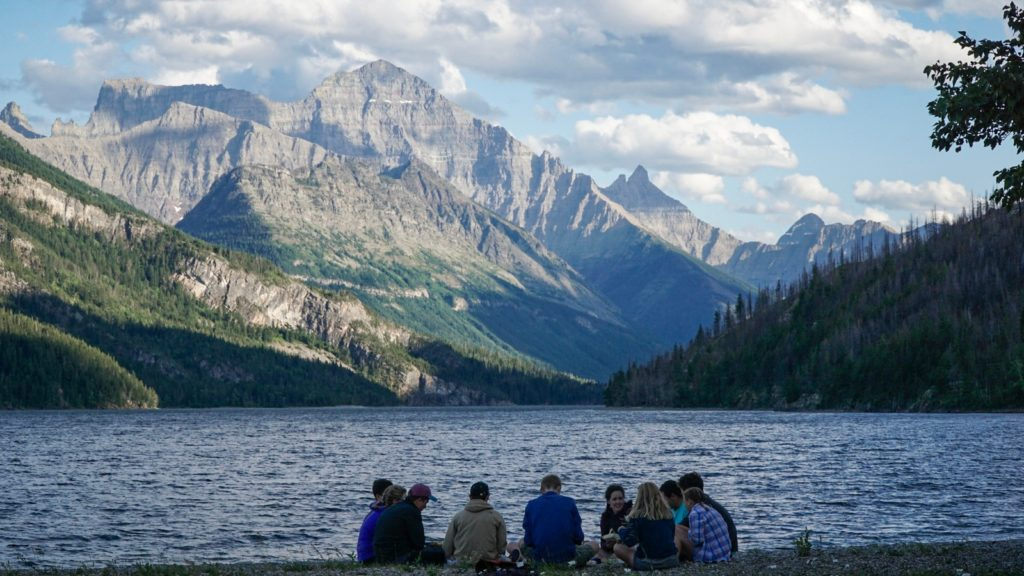A group eats together next to a lake in the Canadian Rockies after biking to their campsite.
