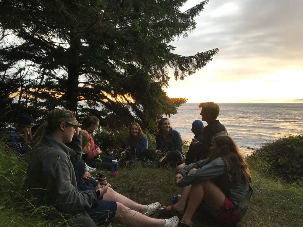 A group of teens during sunset overlooking the Pacific Ocean during their summer hiking trip.