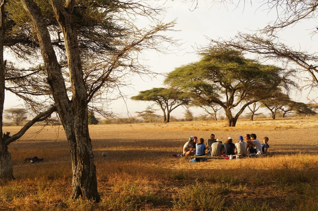A group sits together in the Serengeti of Tanzania during their service and hiking trip.