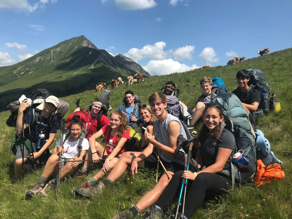Hannah posing with her group on Alpine Challenge while taking a break from hiking