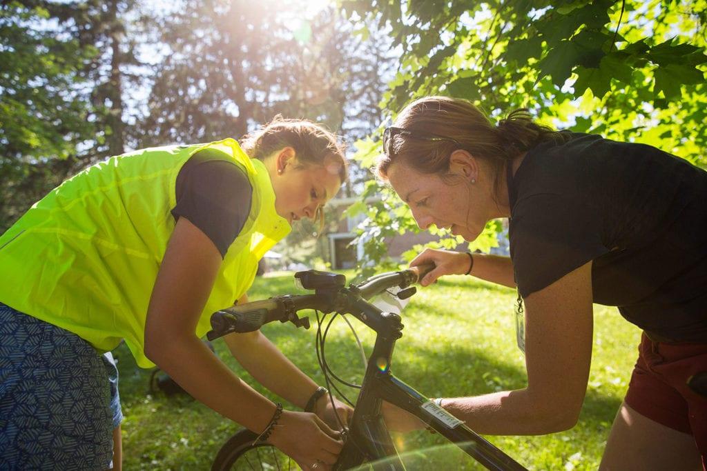 Staff member teachers a leader how to adjust her bike's brakes during training before her biking trip.
