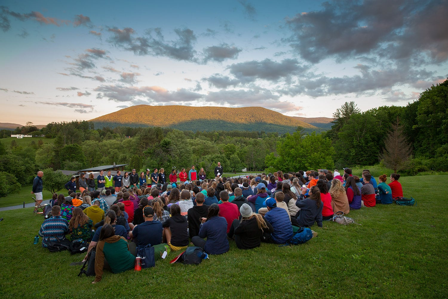 Large group of staff gathered outdoors during training. View of the Berkshire Mountains in the background.