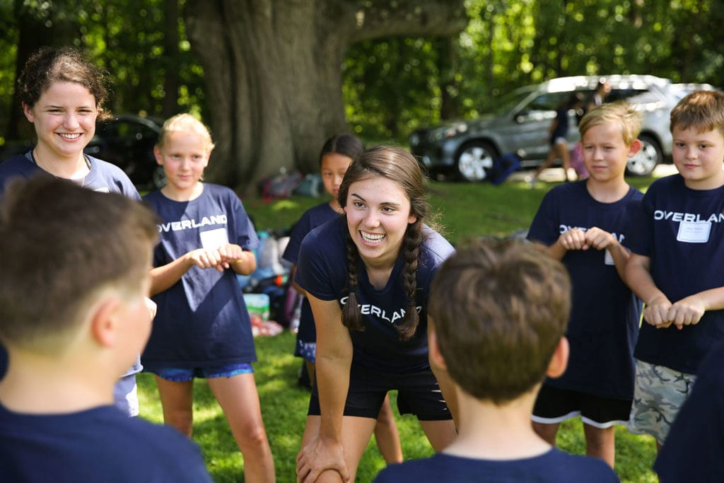 A leader smiling in a circle of 4th and 5th graders while playing a game as they first meet each other before their adventure.